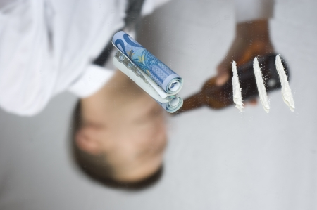 Drugs and money on a mirror. Out of focus reflection of addicted businessman. photo
