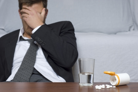 drug abuse: Businessman sitting on the floor. On the table glass of water and pills. Stock Photo