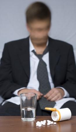 sleeplessness: Uomo d'affari seduta sul pavimento. Pillole sul tavolo. Sfocato e sfondo sfocato.