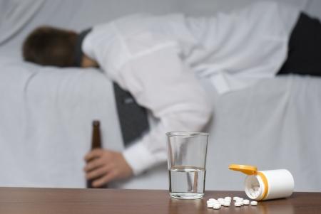 sleeplessness: Bicchiere d'acqua e pillole sul tavolo. Sullo sfondo fuori fuoco un uomo d'affari svenuto sul divano.