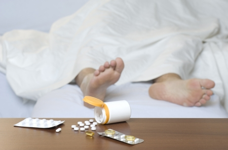 unconscious: Different types of pills on the table. Person sleeping in the background. Stock Photo