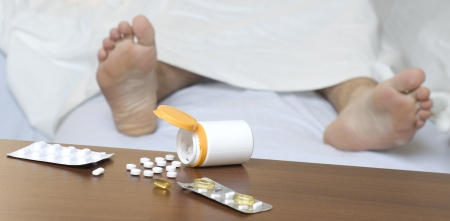Different pills on the table. Person sleeping in the background. Impalanced diagonal composition photo
