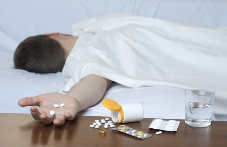 sleeping tablets: Various drugs on the table. Man passed out on the sofa. Stock Photo