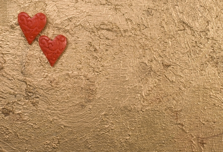 Two red hearts on a golden surface. Space for text. photo