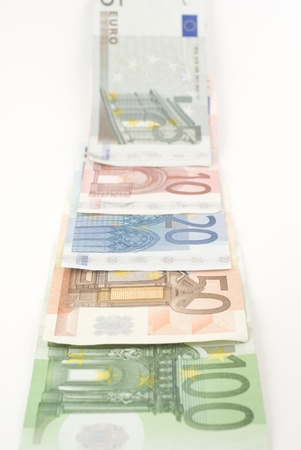 Euro banknotes disappearing in the horizon. Isolated on white.