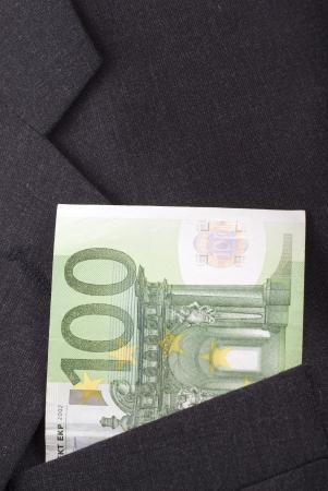 one hundred euro banknote: Un centenar de billetes en euros en el bolsillo de un traje oscuro. Foto de archivo