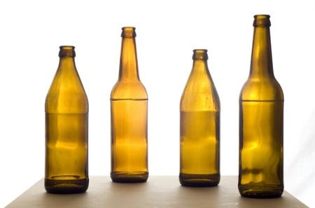 botellas vacias: Cuatro botellas de cerveza vacías en la mesa. Aislado en un fondo blanco.