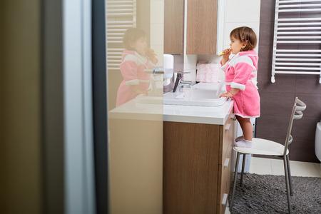 화장실에서 그녀의 이빨을 칫 솔 질하는 어린 소녀.