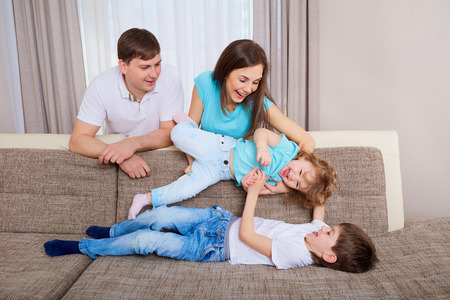 family sofa: Family playing on sofa at home. Stock Photo