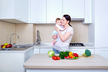 Mother and Baby kissing and hugging at Home. Mom and Her Child in the kitchen .Healthy eating. Diet,dieting concept.