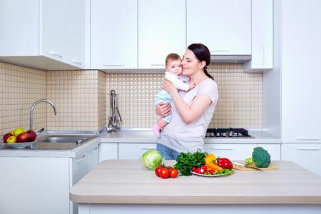Moeder en baby kussen en knuffelen thuis. Moeder en haar kind in de keuken. Gezond eten. Dieet, op dieet zijn concept. Stockfoto