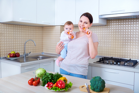 Mother and baby eating carrot in the kitchen.