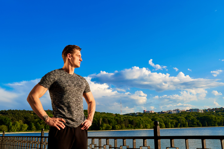 Sports man body figure  with the blue sky in the background. Confident look.