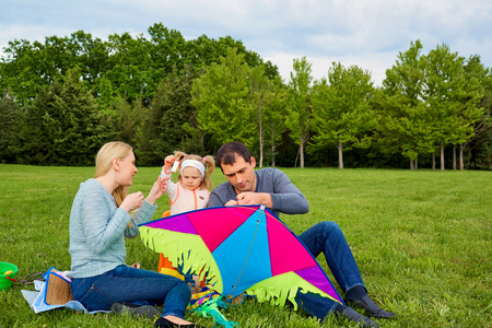 Happy young family with flying a kite in the park.