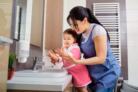 Mother and daughter washing their hands in the bathroom. Care and concern for children. Фото со стока