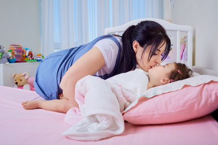family tickle: Baby and mother play, kiss  in the bed.
