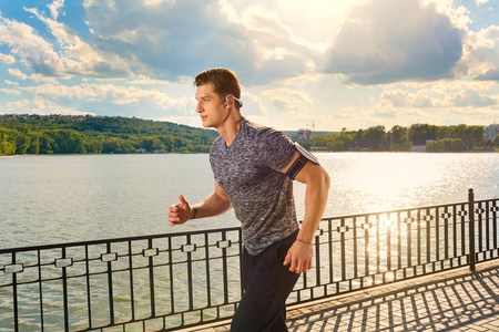 Man running in park during sunny morning. Healthy lifestyle concept. Stock Photo