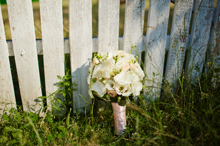 fense: Wedding bouquet on white fense on ceremony place