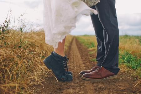Mannelijke en vrouwelijke benen in laarzen in veld. Liefde, kus concept.