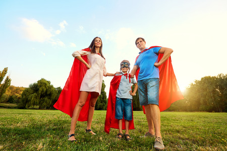 Superheroes family. Mother, father and son in the costumes of superheroes in nature. Mother's Day, Father's. 스톡 콘텐츠