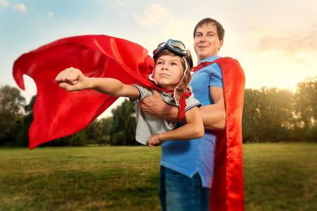 Ojciec i syn grają w kostiumach superhero w parku na przyrodę. Szczęśliwa rodzina. Dzień Ojca.