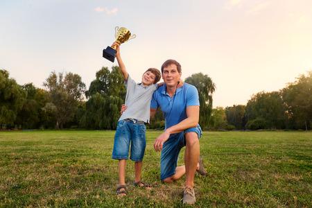 De zoon van een kampioen met een gouden bekerkampioen met zijn vader in het park buiten omarmen in de natuur glimlachen, lachen, plezier, vreugde.