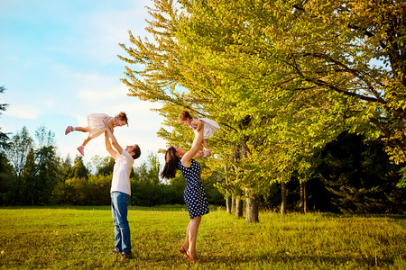 throw up: Happy family in the park outdoors in summer, autumn. Mother, father and daughter spending time together on the grass in the park, the kids throw up fun, joy.