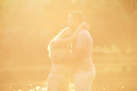 Pregnant couple in the rays of sunlight at sunset. Husband hugs his pregnant wife tenderly. The concept of a happy family, love and pregnancy.