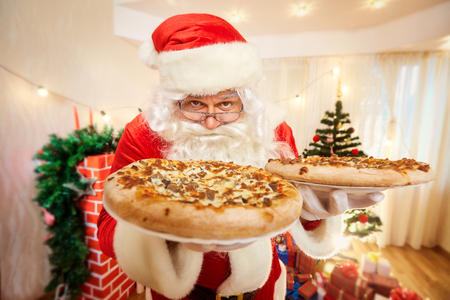 Pizza in the hands of Santa Claus at Christmas, happy new year close-up.
