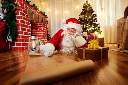 Santa Claus at Christmas, New Years Eve wrote a list of gifts to children on paper in the room with the Christmas tree and fireplace.