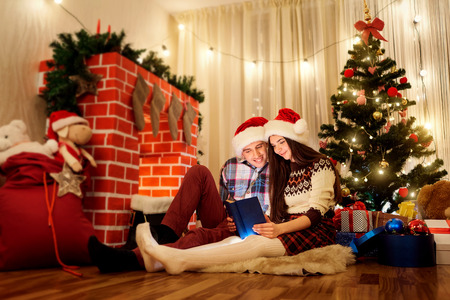 cosily: The Christmas couple in love in hats Santa Claus reading a book by the fireplace and garlands. The concept of a Happy New Year.