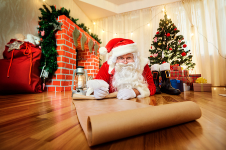 indoor background: Santa Claus at Christmas, New Years Eve wrote a list of gifts to children on paper in the room with the Christmas tree and fireplace.