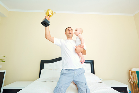 Dad with a baby holding a cup chempionship .Super dad with a child. The concept of parents and childhood.