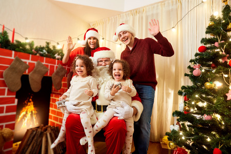 niñas gemelas: Happy family with Santa Claus laughing and smiling. Mother, father, daughter twin girls celebrate Christmas, New Years Eve with Santa in the room with the Christmas decorations,  tree.