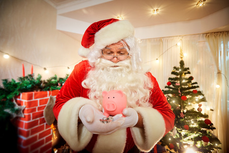 christmas budget: Santa Claus holding a pig piggy bank and coins in Christmas.