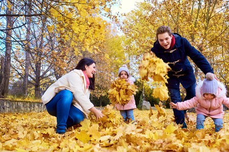 Happy family in autumn park. Mother, father and two little girls on the nature throwing yellow leaves, playing, laughing. The concept of a happy family.