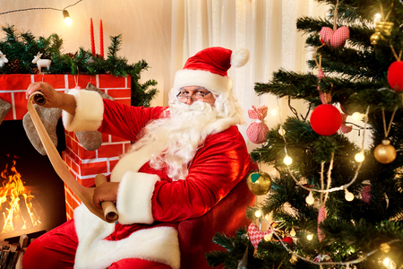 christmas list: Santa Claus in a Christmas list with a gift in the hands of the fireplace and Christmas tree.