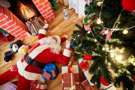 サンタ クロースが眠っている、疲れている、新年、クリスマスの後、暖炉、クリスマス ツリーの近くで飲みます。