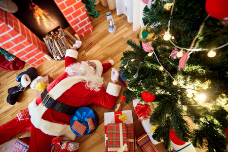 Santa Claus is sleeping, tired, drunk in a room near the fireplace and the Christmas tree after the New Year, Christmas.