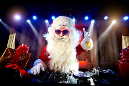 Dj Santa Claus mengt zich op het feest met Kerstmis en stak zijn hand op