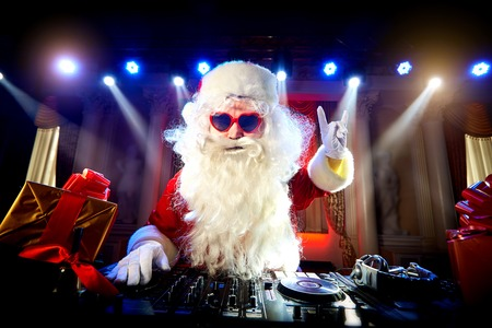 Dj  Santa Claus mixing at the party at Christmas, raised his hand up Stock Photo