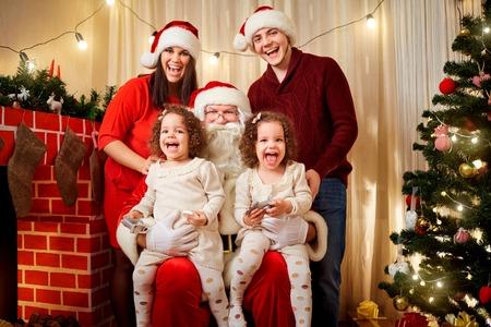 niñas gemelas: La familia feliz con Santa Claus riendo y sonriendo. Madre, padre, hija niñas gemelas celebran la Navidad, la víspera de Año Nuevo con Santa en la habitación con las decoraciones de Navidad, árbol.