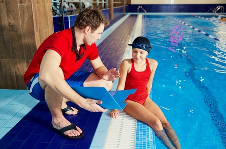 Coach,tranier to swimmer girl at the pool discussing with athlete.