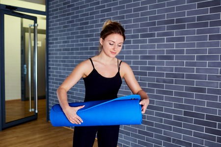 Young girl with mat getting ready to workout, yoga.