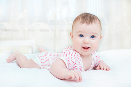 かわいい赤ちゃんが、白いベッドの上で横になって笑っています。