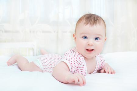 Leuke baby die terwijl het liggen op een wit bed glimlacht.