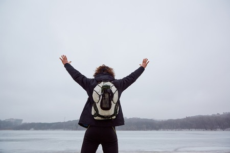 The concept of travel, adventure, freedom. A man with a backpack put his hands up in  frozen lake winter.
