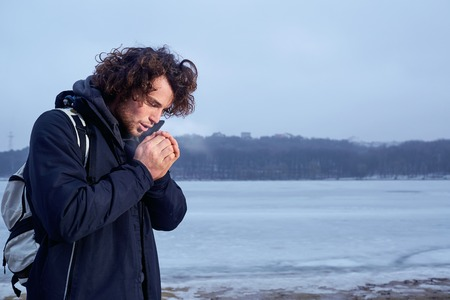 The concept of cold, frost. Curly haired young man warming his hands in winter outdoors.