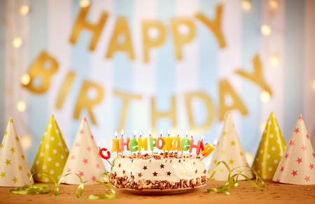Happy birthday cake with candles Russian letters on the background of garlands. Stock Photo