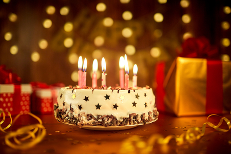 Happy birthday cake with candles on the background of garlands and letters. Stock Photo